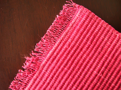 Modern dolls' house miniature floor rug made out of a pink woven place mat.