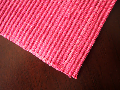 Piece of pink woven placement, cut along a line of zig zag stitching, and three rows up at the top.