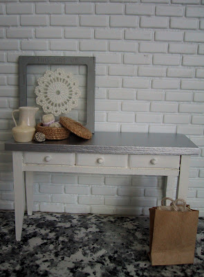 Modern dolls' house white and zinc side table, displayed against a white brick wall, with a selection of white, grey and natural miniature accessories displayed on top.