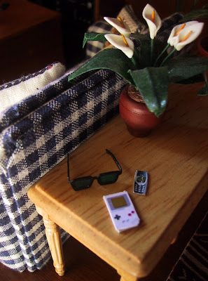 Modern dolls' house miniature side table behind a blue and white checked sofa. On the table is a potted lilly plant, a pair of sunglasses, a Gameboy and a Nokia mobile phone.