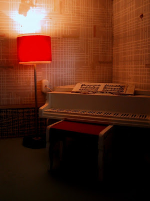Vintage 1967 Lundby dollshouse study area with grand piano and desk with chair, lit up at night.