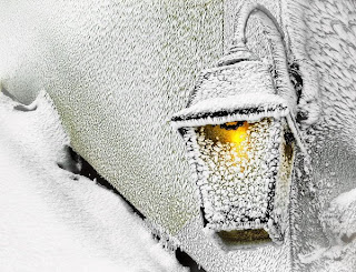 Горящий уличный фонарь весь в снегу.