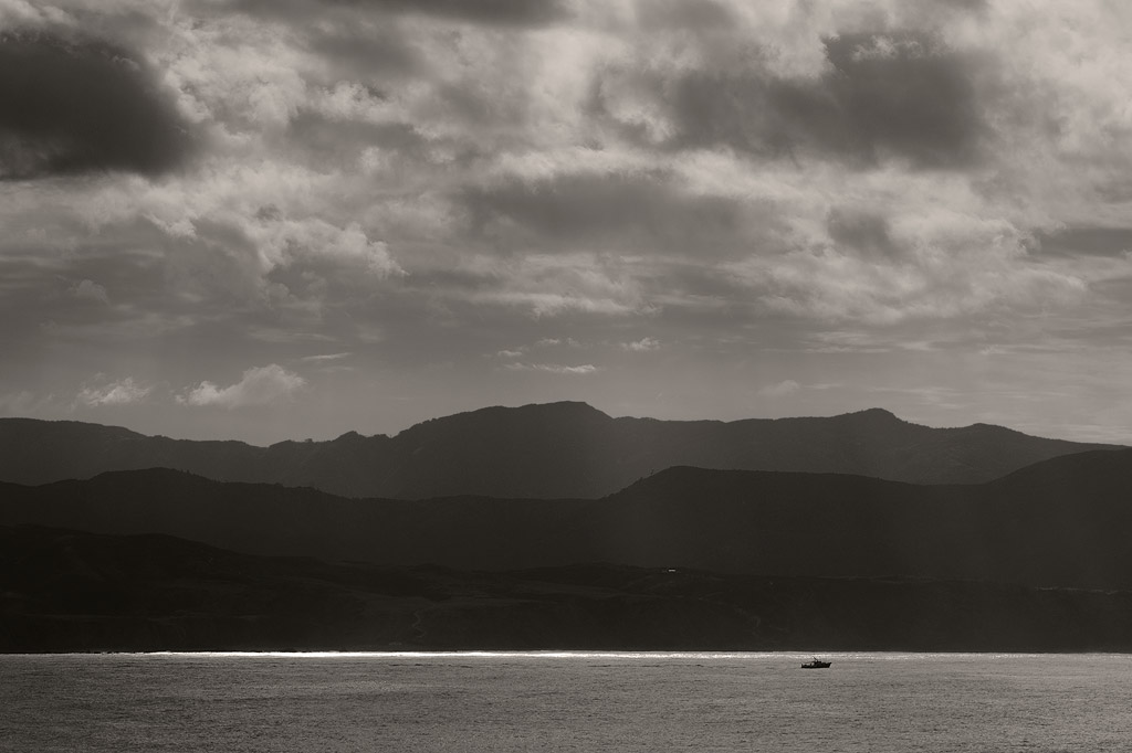 Sailing past Pencarrow Head, the Rimutaka Range beyond.