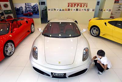 Una trabajadora china limpiando un Ferrari en un concesionario de Pekin