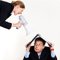 manager with megaphone yelling at employee hiding