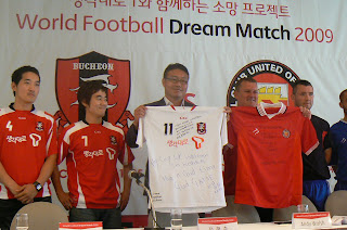 Bucheon and FC United coaches swap shirts.