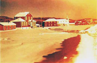 Sanmaur - L'école, le presbytère, l'église, le magasin Thériault, fin d'apràs-midi d'hiver, vers 1953. Photo aimablement retouchée par Paul-Émile Larivière