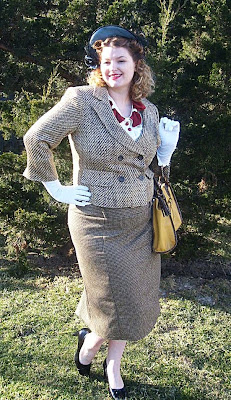 1940s style suit and hat with veil and a mustard handbag
