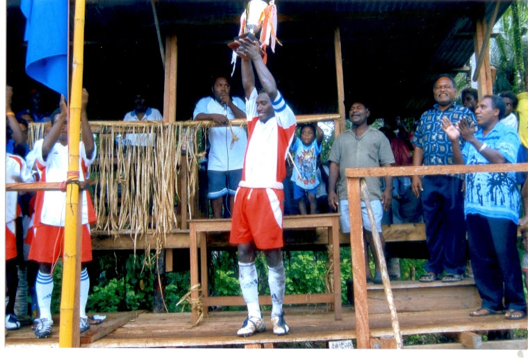 Santos FC Captain Mr. Augustine Rukarae hoisting high the trophy (1st Prize) won by Wairokai Club