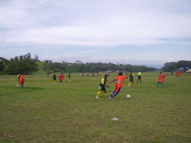 Santos FC Midfielder Mike Hui (in orange jersey) with the ball up against a LAS United FC player
