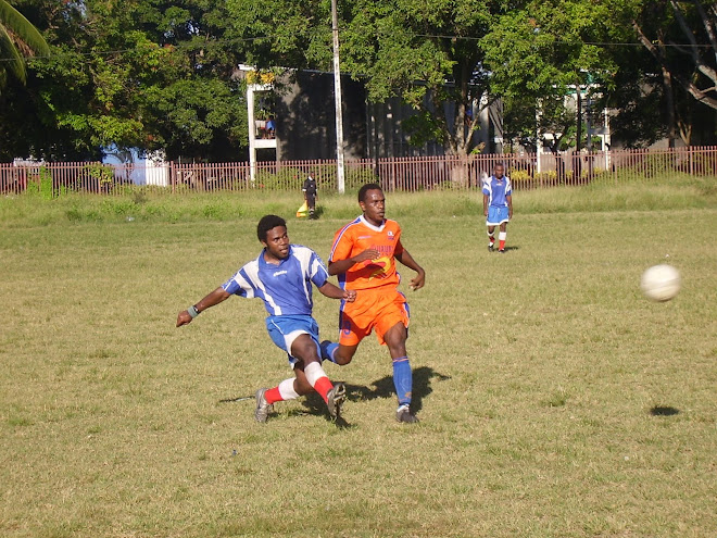Northern United last man clears the ball from the advancing Santos FC striker Apollos