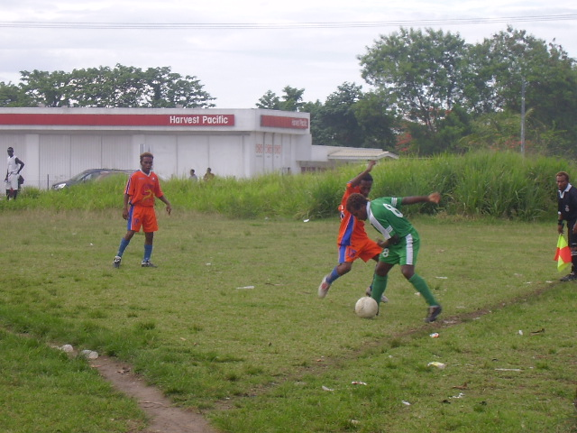 SANTOS STRIKER LESLIE CONTESTING THE BALL AGAINST A DMP PLAYER WHILST BEING WATCHED BY JASON