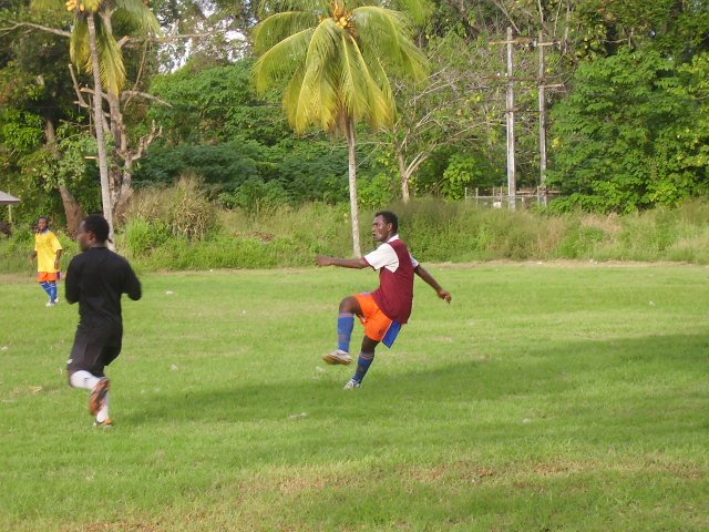 Santos FC Sweeper Cornelius (in orange plants) clearing the ball