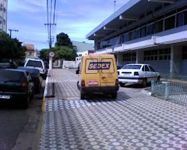 Carros dos Correios na calçada