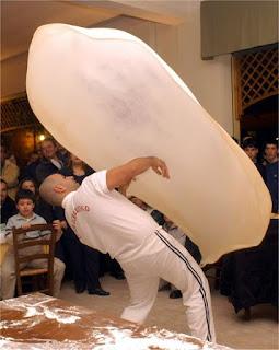 un pizzero haciendo una demostración de sus habilidades