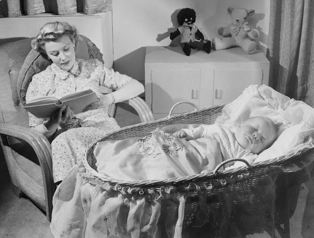 Woman reads as baby sleeps. Photographic Advertising Limited. Collection of National Media Museum. Photographic Advertising Limited (1929-1977) created stock advertising images with the potential for selling a range of products. Idyllic household and family scenes were very popular, photography-news.com, photography news, Diana Topan, International Children's Day, June 1, vintage baby photos
