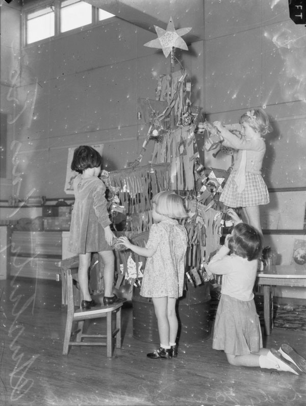 Christmas in Melbourne, Australia, 1942. Four little girls decorate their austerity Christmas tree at a suburban school. The tree branches are constructed of sticks hung with fringed paper and foil stars are used as decorations.