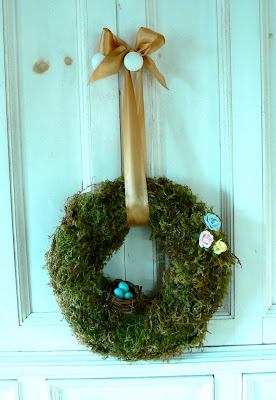 a mossy spring wreath with paper roses and blue robin's eggs