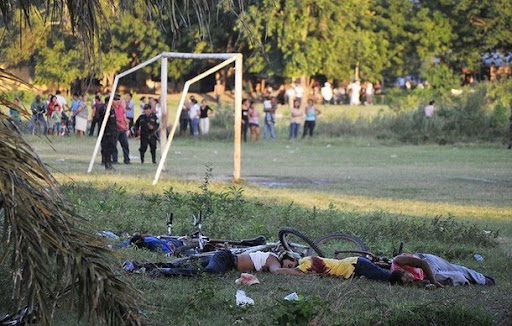 Lifeless bodies are seen at the crime scene where 14 people were killed while watching an amateur soccer match