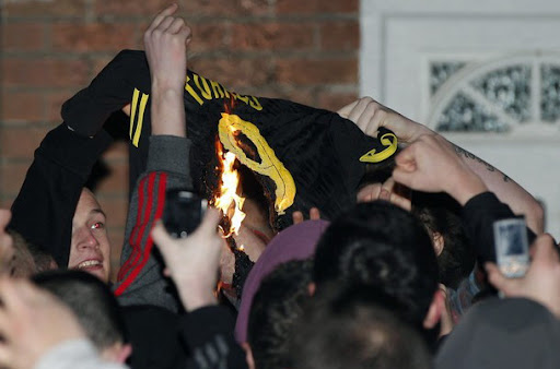 Liverpool fans burn a Fernando Torres number nine shirt outside the club's training ground