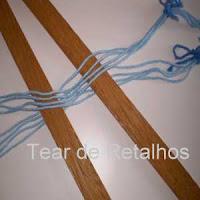 Foto mostrando os fios do urdume separados, na cruzada, por duas réguas, preparando os fios para a colocação no tear.