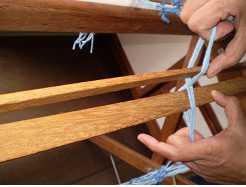 """Foto mostrando como colocar as duas réguas entre os fios da """"cruzada"""" para preparar os fios do urdume para serem colocados no tear."""