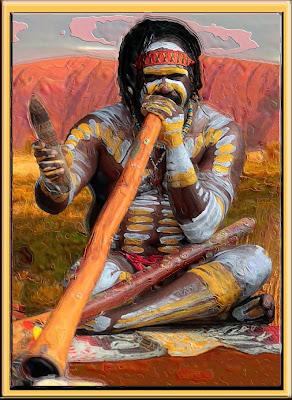 Australian Aborigine playing a dijiridu with Uluru (Ayers Rock) in background.