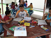 Some of the kids at the orphanage playing with coloring books and other gifts.