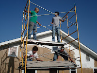 Some of the guys putting together a scaffold so the girls can paint.