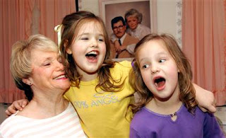 5-year-old twins Carli Sue Morgan, left, and Margaret Jan Marie, sing a silly song for their 63-year-old mother Judy Cates