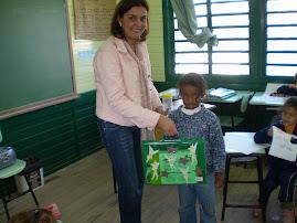 A professora Rejane entregando a Maletinha Mágica para a aluna Vitória.