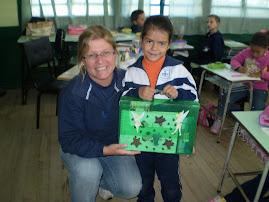 Aluna Hérika entregando a Maletinha Mágica para a professora Adriane