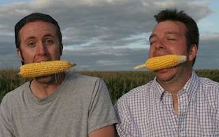Photo of Curt and Ian with ears of corn in their mouths
