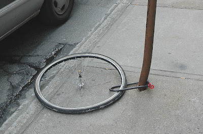 Image of bike wheel locked to pole, evidence of theft of bicycle
