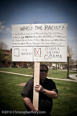 Beefy man holding big sign with lots of words making claims about Obama's support for terrorists
