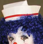 Old-fashioned nurse's hat worn by a clown with blue hair