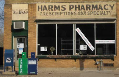 Storefront with early to mid-20th century sign that reads Harms Pharmacy