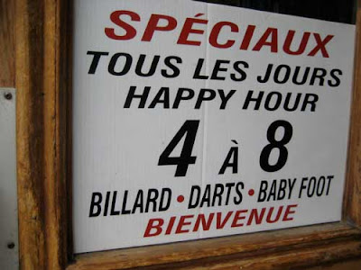 Happy hour sign at a bar listing Billiards, Darts and Baby Foot