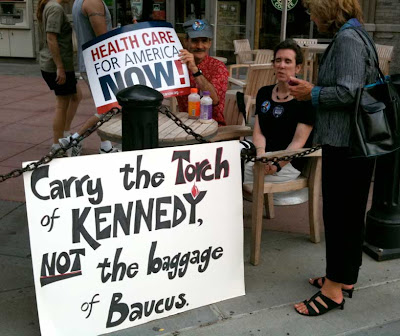 Couple with a sign reading Carry the torch of Kennedy, not the baggage of Baucus