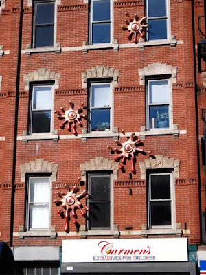 Five shiny metal sculptures that look like splatted amoebas attached to a brick commercial building