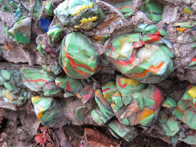Multi-colored green, red, yellow and white glass chunks embedded into the red rocks