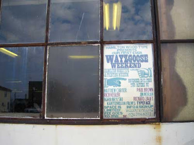 Woodtype printed sign for the Wayzgoose in the window of the museum