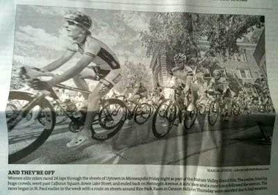Black and white newspaper clipping of a bunch of serious-looking bicyclists in a race
