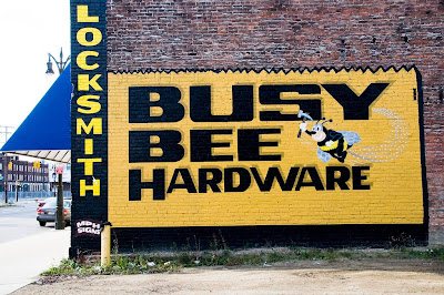 Yellow and black hand-painted Busy Bee Hardware sign on brick building