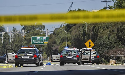 Police tape and four patrol cars surrounding a white pickup truck