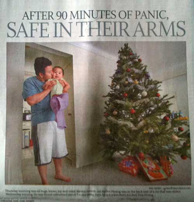 Star Tribune photo of a young Asian man hugging and kissing a baby by a Christmas tree