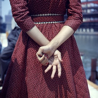Young woman in dark red dress with white dots, shot from the back, no head shown, her hands clasped and her fingers making a sign of some sort