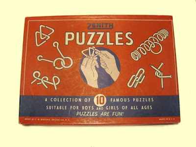 Red cardboard Zenith Puzzles box with illustrations of hands and metal puzzles