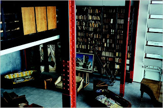 The bookcase with metal shelving has a ladder that slides along the length of the shelves. The cupboards and bookshelves were designed as screens to the second floor