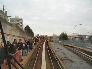Skytrain passengers walk beside tracks to Columbia Station